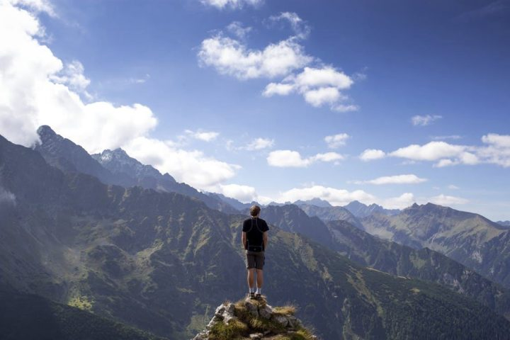 man standing on cliff in front of blue mountain view with clouds